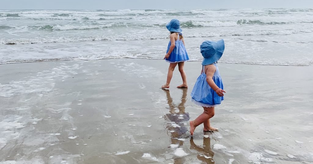 Two girls wearing blue dresses and blue hats walking in the water at the ocean.