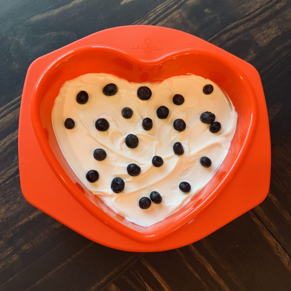 cake pan with plain yogurt spread evenly and blueberries sprinkled on top
