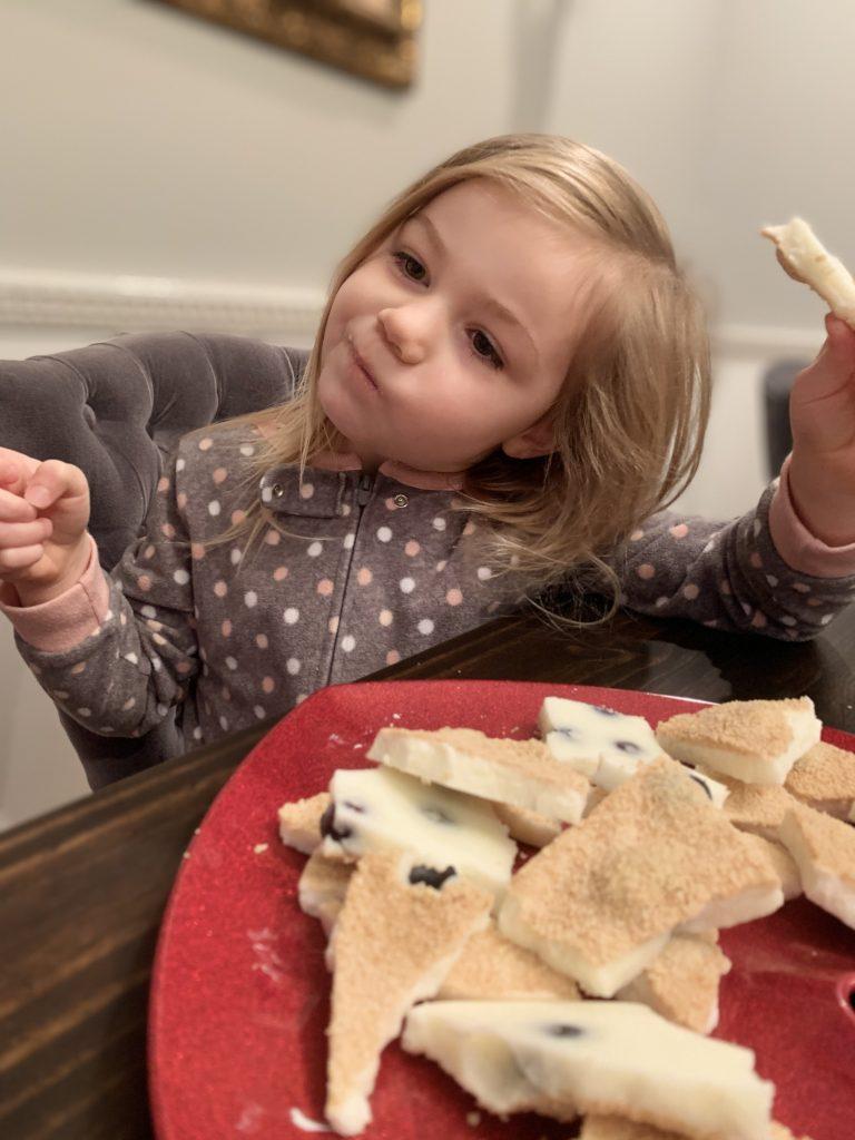 happy little girl eating yogurt bark