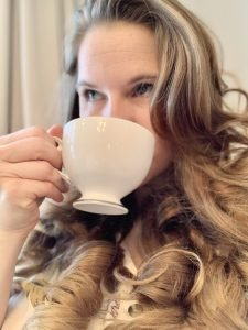 Allison, of Darling and Dapper Life, sipping out of a teacup.