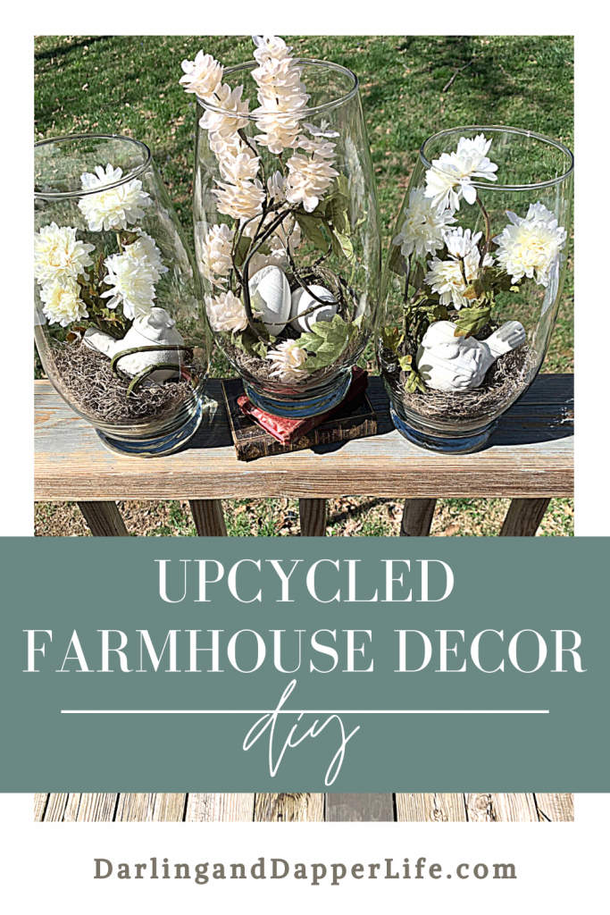"""3 piece vase set filled with spanish moss, white flowers, white eggs and ceramic birds. Shown on top of deck railing with grass in the background and title that reads, """"Upcycled Farmhouse Décor DIY""""."""