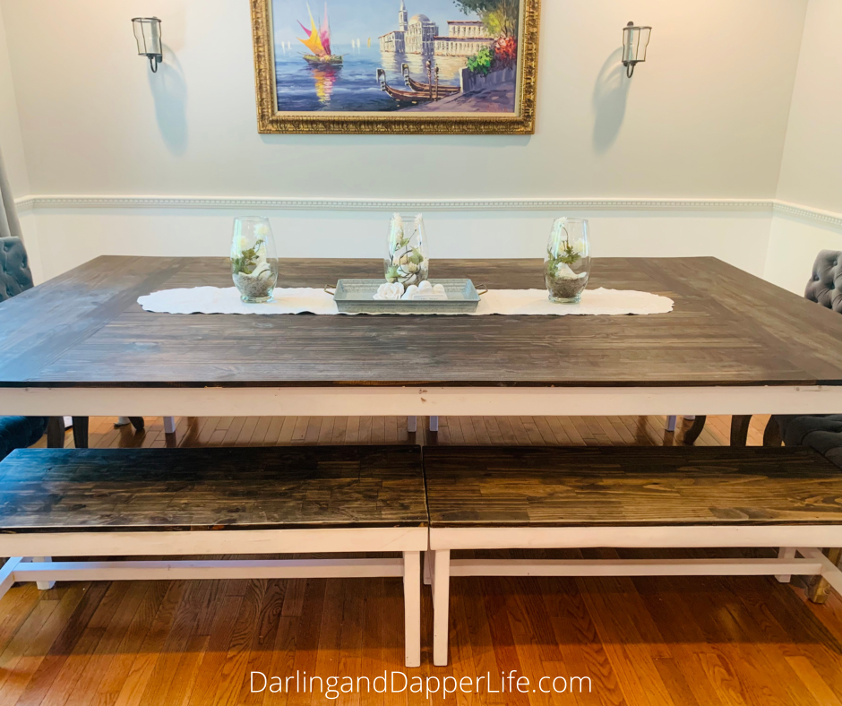 Rustic Farmhouse table centerpiece of three hurricane vases and a galvanized tray on top of a natural linen colored runner. Showing table, two benches, two end chairs, and on the wall behind them one seascape painting and two sconces.