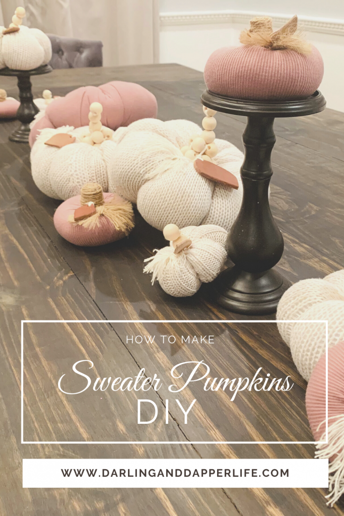 """Title page showing pink and ivory fabric pumpkins made out of recycled sweaters on a dinning table. Printed on the image is the title, """"How to Make Sweater Pumpkins DIY""""."""